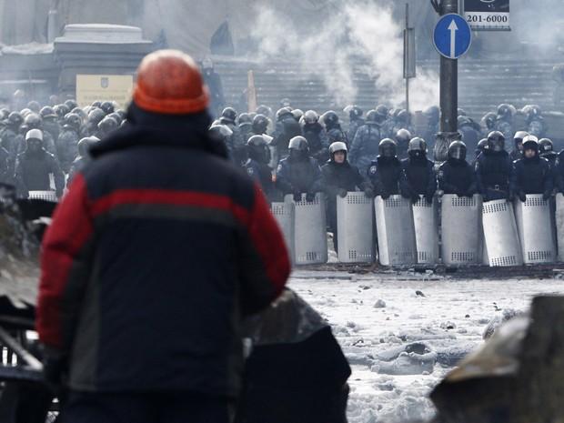 Um manifestante observa barreira montada pela polícia de choque em local dos confrontos em Kiev. (Foto: David Mdzinarishvili/Reuters)