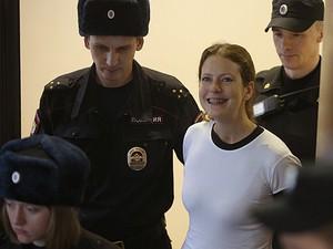 Ativista brasileira Ana Paula Maciel é escoltada por policiais russos (Foto: Evgeny Feldman/AP)