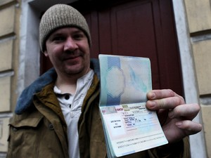 O britânico Anthony Perrett, primeiro militante do Greenpeace a receber visto russo, mostra seu passaporte com o visto russo. (Foto: AFP Photo/Olga Maltseva)