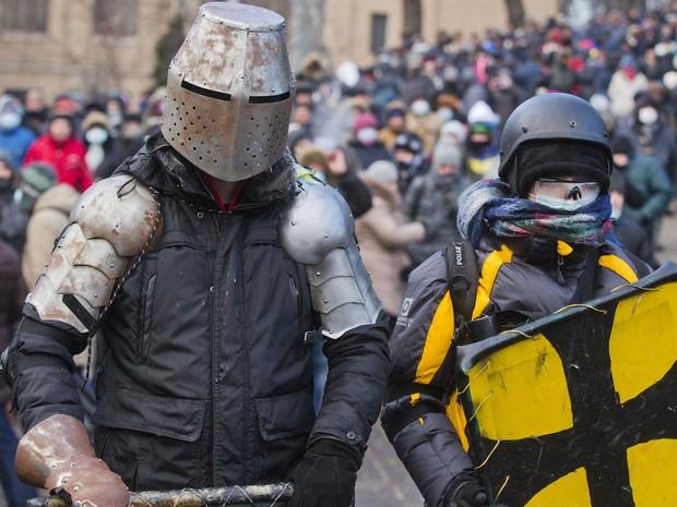 Manifestantes improvisam proteções para o corpo que lembram trajes de gladiadores durante protesto e confrontos com a polícia no centro de Kiev, na Ucrânia. Após a noite de sérios conflitos nas ruas, um grande grupo voltou a se aglomerar para protestar. (Foto: Evgeny Feldman/AP)