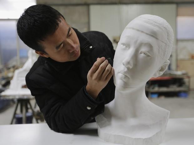 Li Hongbo usa uma agulha para tirar o pó de uma de suas esculturas de papel em Pequim, na China (Foto: Jason Lee/Reuters)
