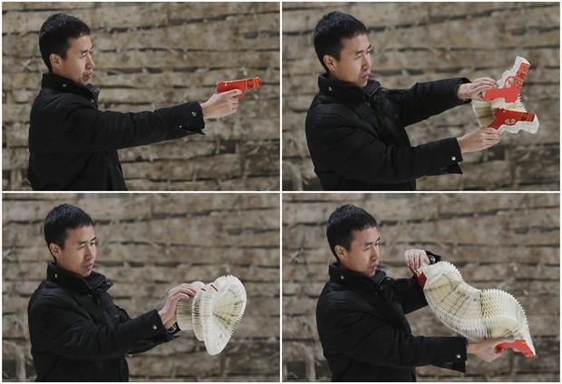 'A arma é sólida, usada para matar, mas a transformei em uma peça de decoração', explica Li Hongbo, enquanto brinca com o formato da escultura de papel (Foto: Jason Lee/Reuters)