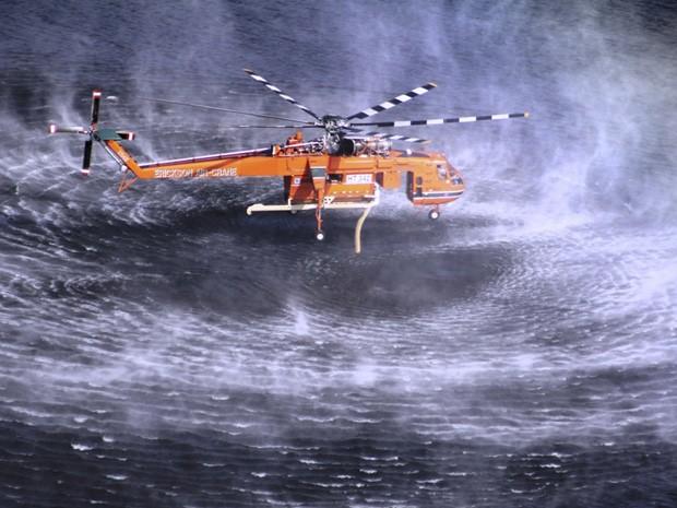 Avião capta água para combater as chamas em um incêndio de grandes proporções na Austrália. (Foto: Country Fire Authority/AP)