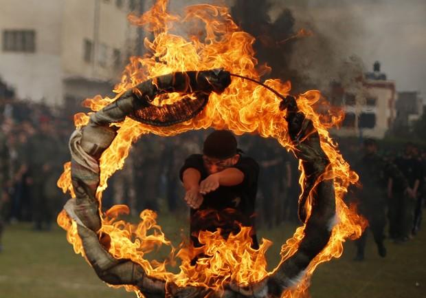 Estudante 'faz careta' ao saltar por círculo de fogo durante cerimônia militar na Palestina (Foto: Suhaib Salem/Reuters)