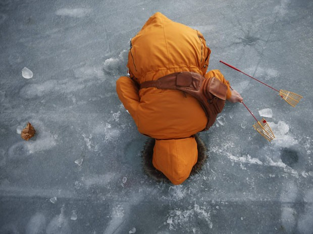 Mulher pesca em lago congelado em festival na Coreia do Sul iniciado neste sábado (4) (Foto: Kim Hong-Ji/Reuters)