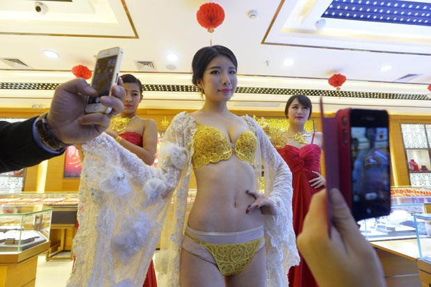 Modelo usa lingerie de ouro durante evento promocional na província de Hubei, na China (Foto: Reuters)