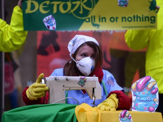 Ativista do Greenpeace faz protesto para alertar presença de produtos tóxicos em roupas infantis (Foto: Attila Kisbenedek/AFP)