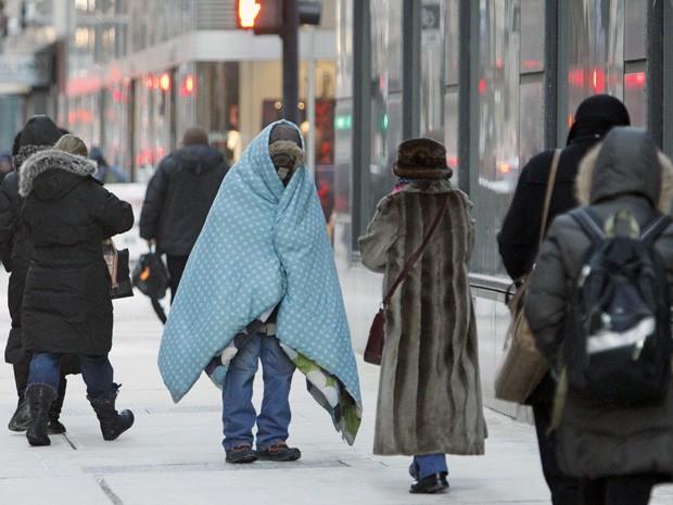 Morador de rua se enrola em cobertor para enfrentar o frio em Chicago nesta terça-feira (28). (Foto: Kiichiro Sato/AP)