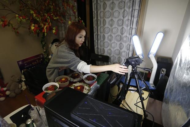 Conhecida como 'A Diva', Park Seo-yeon ajusta a câmera para comer diante de milhares de espectadores, em uma prática lucrativa que está se tornando moda na Coreia do Sul (Foto: Kim Hong-Ji/Reuters)