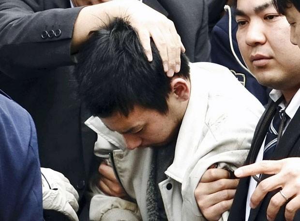 Yuta Sugimoto é levado por policiais após ser detido nesta quinta-feira (8). Perseguição de dois dias envolveu 4 mil policiais e 900 carros. Ele é acusado de ter participado de estupro coletivo (Foto: Kyodo News/AP)