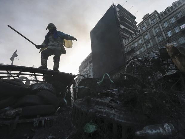 Manifestante é visto em barricada no centro de Kiev, na Ucrânia, neste domingo (Foto: Konstantin Chernichkin/Reuters)
