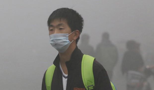 Jovem usa máscara para evitar riscos à saúde provocados pela poluição na China. (Foto: China Out/AFP)