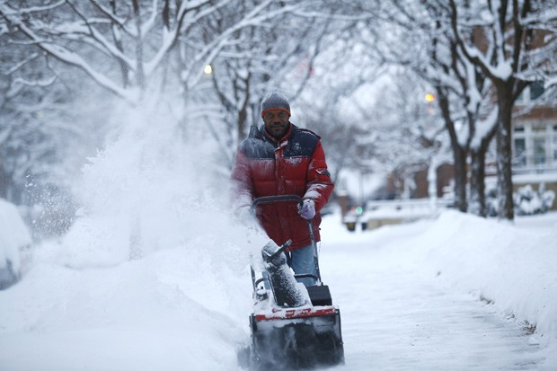 Foto tirada nesta segunda-feira (6) mostra homem retirando neve de uma calçada de Detroit, em Michigan, nos Estados Unidos. O estado foi atingido por uma grande tempestade de neve. (Foto: Joshua Lott/Getty Images/AFP)