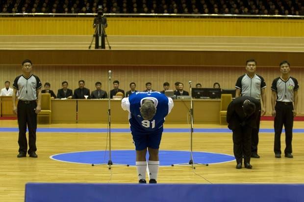 Dennis Rodman curva-se diante do líder norte-coreano Kim Jong-un antes do início da partida comemorativa de seu aniversário (Foto: Kim Kwang Hyon/AP)