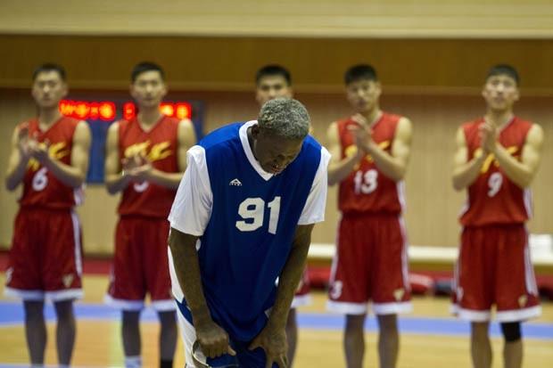 Dennis Rodman curva-se diante do líder norte-coreano Kim Jong-un após cantar 'Parabéns a você', antes do início da partida comemorativa de seu aniversário (Foto: Kim Kwang Hyon/AP)