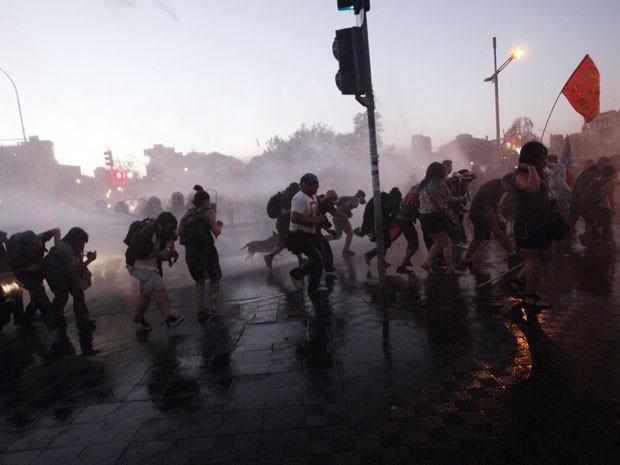 Jato de água dispersa manifestantes que participaram do protesto em Santiago no sexto aniversário da morte do estudante chileno Matías Catrileo (Foto: Luis Hidalgo/AP)