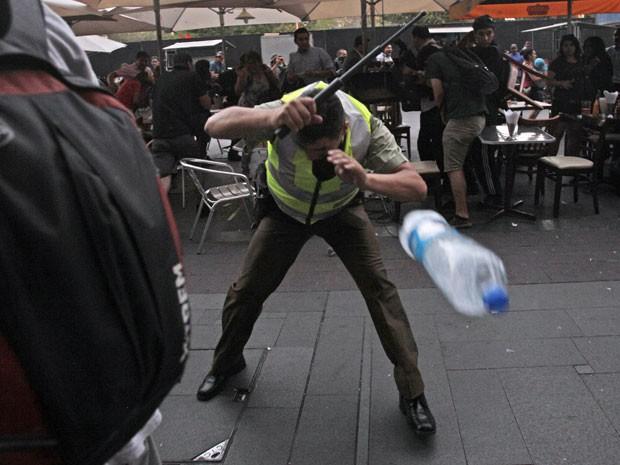 Policial chileno durante protesto em Santiago nesta sexta-feira (3) que marcou o sexto aniversário da morte do estudante Matías Catrileo (Foto: Luis Hidalgo/AP)