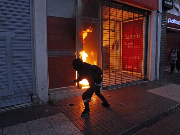 Manifestante lança bomba em banco durante protesto em Santiago no sexto aniversário da morte do estudante universitário chileno Matías Catrileo (Foto: Luis Hidalgo/AP)