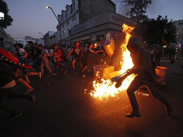 Manifestantes põem fogo em barricada durante protesto em Santiago nesta sexta-feira (3); eles protestaram durante o sexto aniversário da morte de Matías Catrileo, universidade de origem mapuche assassinado por policial em 2008 (Foto: Luis Hidalgo/AP)