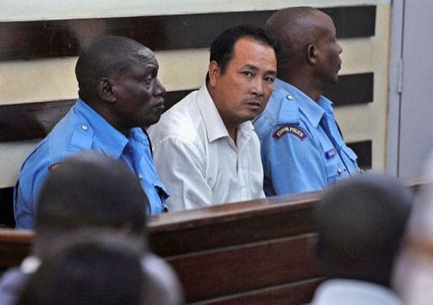 O chinês Tang Yong Jian (ao centro) é visto durante o julgamento realizado em Nairóbi, no Quênia, nesta segunda-feira (27) (Foto: Tony Karumba/AFP)