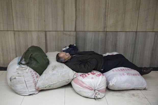 Passageiro usou bagagem para montar 'cama king size' em estação de trem em Pequim, na China (Foto: Alexander F. Yuan/AP)