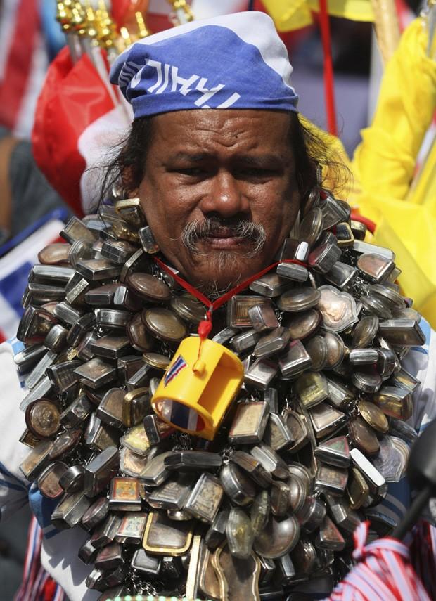 Homem foi flagrado desfilando com pescoço 'supercarregado' de amuletos em Bangcoc, na Tailândia (Foto: Sakchai Lalit/AP)