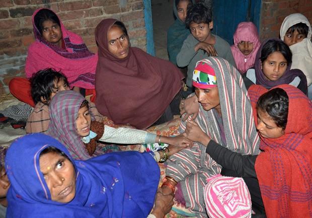 Foto de 7 de janeiro mostra parentes confortando a mãe de Shobha Singh, morta por um tigre mo vilarejo de Chedri Akbarpur, no distrito de Sambhal, no estado de Uttar Pradesh; ela é uma das oito vítimas do animal. (Foto: AP Photo)