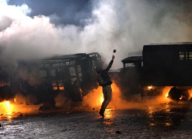 Manifestante é flagrado lançando bomba contra policias em praça de Kiev (Foto: Sergei Supinsky/AFP)