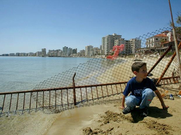 Em foto de 2003, garoto grego-cipriota posa em frente à cerca que separa área abandonada de Varosha (Foto: AP Photo/Petros Karadjias)