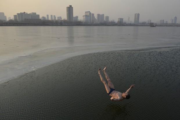 Senhor de 74 anos saltou em rio congelado durante exercícios vespertinos em Taiyuan, na China (Foto: Stinger/Reuters)