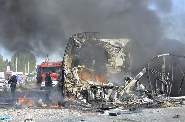 Bombeiros apagam as chamas de ônibus de passageiros que colidiu com caminhão na Argentina, deixando 17 mortos (Foto: Los Andes/Ap)