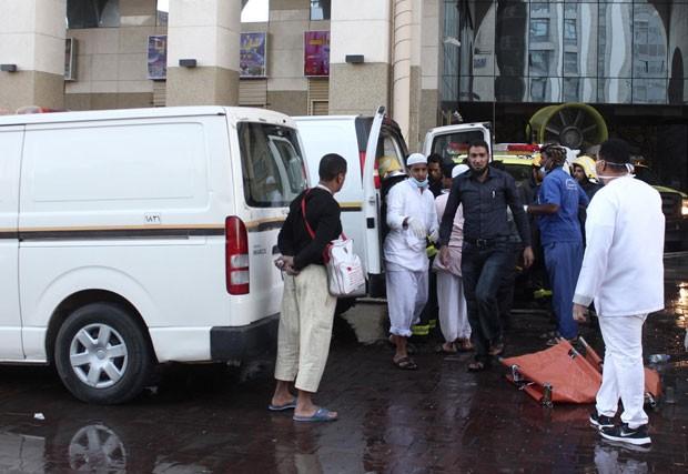 Autoridades ajudam a evacuar pessoas feridas de dentro de hotel em Medina, na Arábia Saudita, que foi atingido por incêndio (Foto: Reuters)