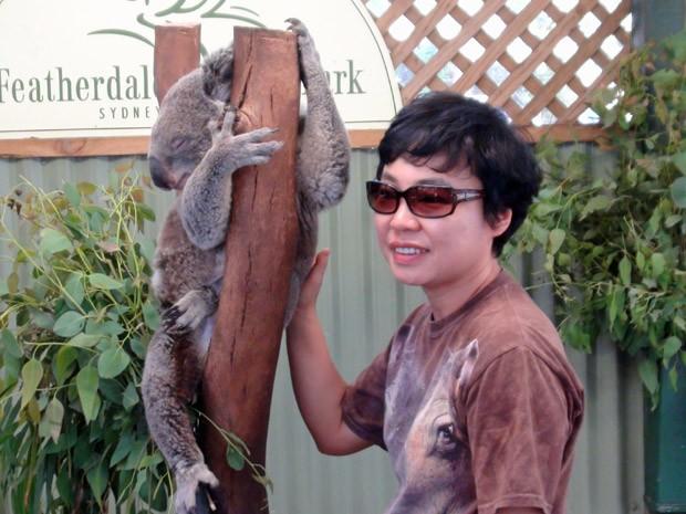 Turista tira foto com coala no Featherdale Park, perto de Sydney; nessa região não é possível abraçar o bicho, mas dá para tocá-lo levemente para a imagem (Foto: Flávia Mantovani/G1)
