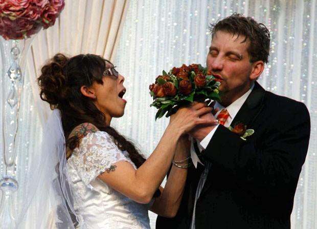 Craig Roush dá uma mordida no buquê de bacon de April DaVila durante a cerimônia de casamento realizada no Blue Ribbon Bacon Festival em Des Moines, nos EUA (Foto: The Des Moines Register, Scott Morgan/AP)