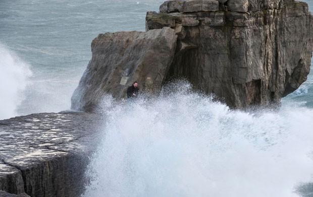 Os dois tentaram escapar das ondas se escondendo nas rochas, mas foram atingidos pela água (Foto: BNPS)