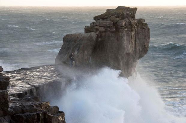 Pai e filho se arriscam em rochas em meio ao mar agitado em Portland, Dorset, na Inglaterra (Foto: BNPS)