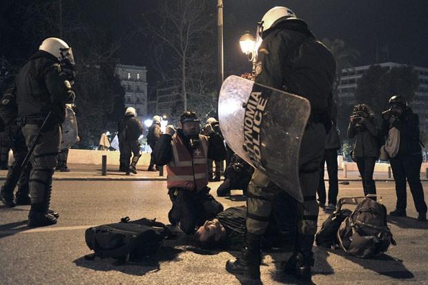 Médico atende ativista antifascista atingido por policiais que o detiveram no centro de Atenas neste sábado (1). (Foto: Louisa Gouliamaki/AFP)