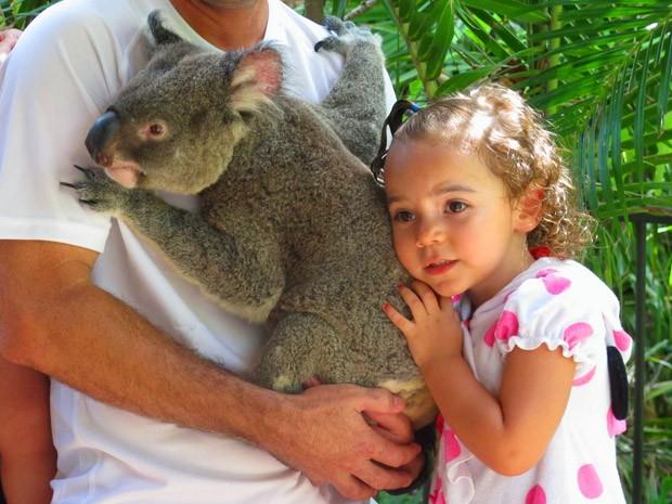 Crianças tiram foto abraçada com coala no parque de Hamilton Island (Foto: Flávia Mantovani/G1)