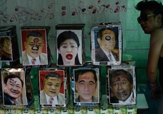 Manifestantes pintam fotos de políticos em protesto na Tailândia (Foto: Christophe Archambault/AFP)