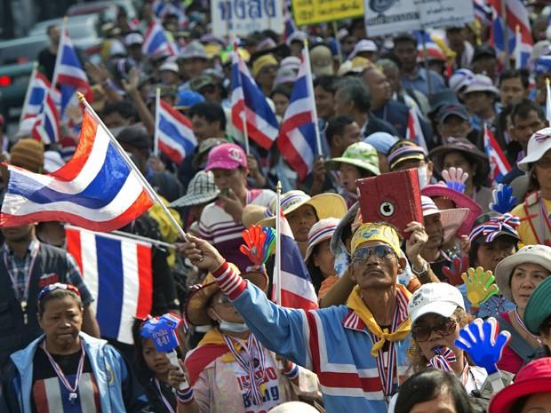 Tailandeses que não conseguiram votar mostram identidades e gritam para policiais em Bangcoc, neste domingo (2) (Foto: Nicolas Asfouri/AFP)