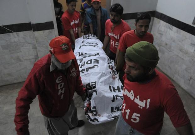 Voluntários carregam o corpo de uma das vítimas do tiroteiro em Carachi, no Paquistão (Foto: Tizwan Tabassum/AFP)