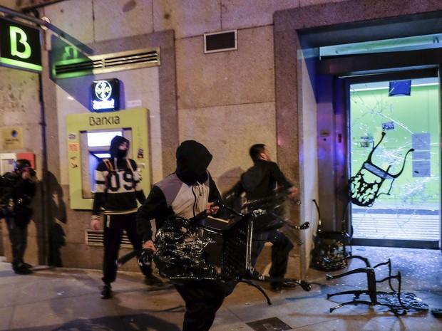 Mascarados atiram cadeiras em vidraça de banco, em Madri, na Espanha (Foto: Pedro Armestre/ AFP)