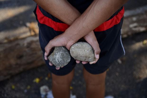 Ativista contra o governo de Nicolás Maduro segura pedras durante protesto na cidade de San Cristóbal nesta quinta-feira (6) (Foto: Leo Ramirez/AFP)