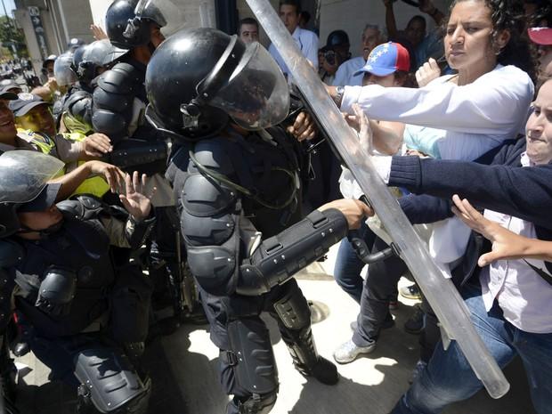 Trabalhadores da saúde pública venezuelana brigam com a polícia de choque durante um protesto em Caracas. (Foto: Juan Barreto/AFP)