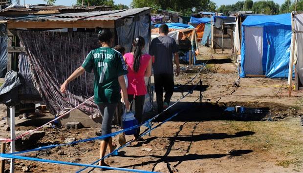 Jovens passam por tendas construídas em assentamento que agora se chama 'Papa Francisco', em Buenos Aires (Foto: Daniel Garcia/AFP)