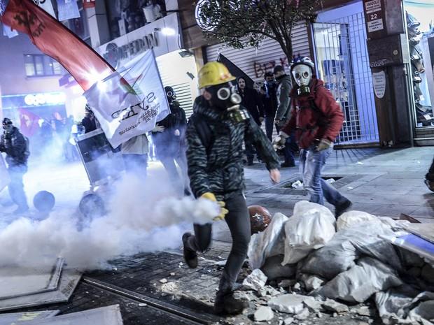 Manifestantes jogam bombas em direção aos policiais (Foto: Bulent Kilic/AFP)