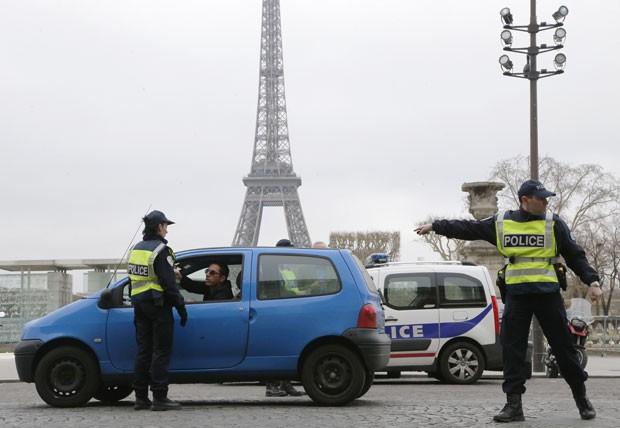 Policiais controlam a passagem de carros em Paris nesta segunda-feira (17); poluição levou governo a estabelecer rodízio de carros (Foto: Francois Guillot/AFP)