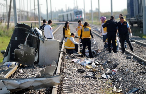 Equipes de resgate trabalham em local de colisão entre ônibus e trem em Mersin, na Turquia, nesta quinta-feira (20); dez pessoas morreram. (Foto: AFP)