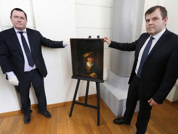 O coronel Stephane Gauffeny, do Departamento Central de Luta contra o Tráfico de Bens Culturais (OCBC), e o comissário Phillippe Frizon, da polícia de Nice, exibem à imprensa o quadro 'O menino e a bolha de sabão', de Rembrandt, em Nice, na França (Foto: AFP Photo/Valery Hache)
