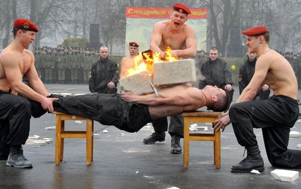 Soldado 'machão' quebra concreto em chamas sobre o peito em Belarus (Foto: Viktor Drachev/AFP)